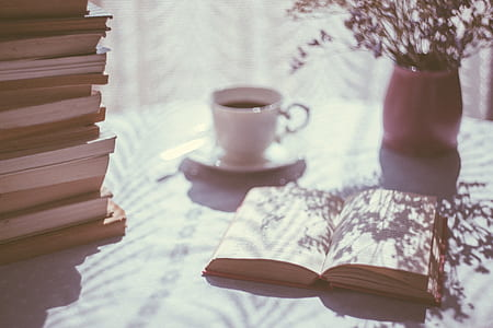 open book beside white ceramic mug and pink ceramic vase on top of table