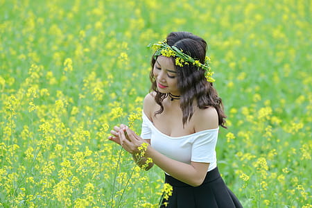 woman in white and black dress standing in flower field