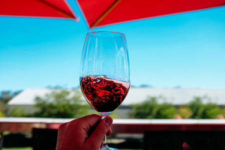Glass of red wine being held against a blue sky