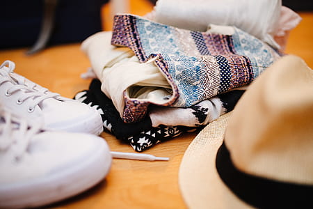 closeup photo of shoes, clothes, and hat on wooden surface