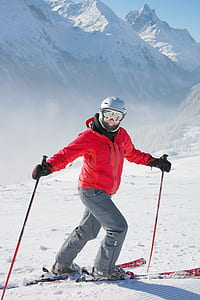 man wearing red zip-up jacket and gray pants with skiblades on snow