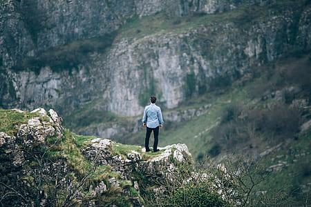 man in blue dress shirt standing on brown mountain