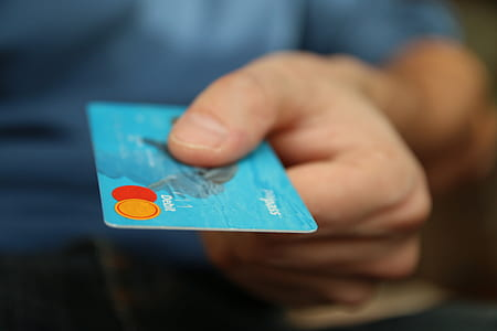 person holding blue MasterCard credit card