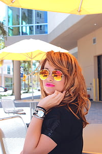 shallow focus photography of orange haired woman wearing aviator sunglasses