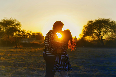 couple kissing on grass field during sunset