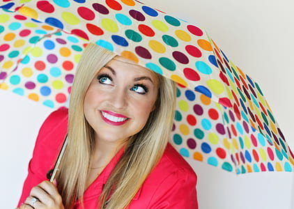 woman wearing red dress holding multicolored folding umbrella