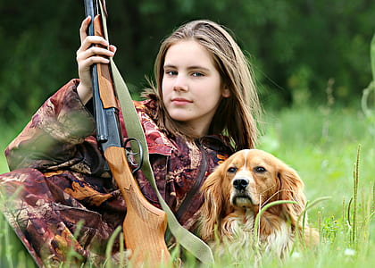 woman with red tree camouflage suit holding brown hunting rifle beside orange and white Welsh springer spaniel on grass field during daytime