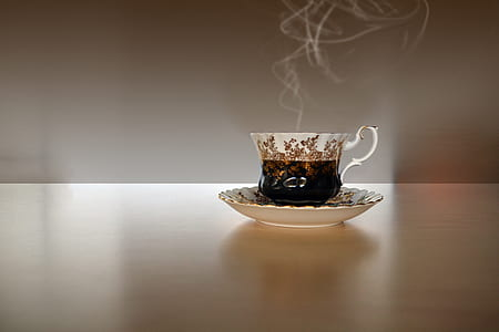 white-and-black ceramic teacup on saucer