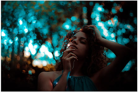 selective focus photography of woman in teal sleeveless top holding white string lights with bokeh brackground