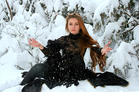 woman wearing black long-sleeved dress on top of snowfield