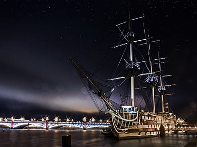 galleon ship sailing on body of water near bridge under stars nighttime