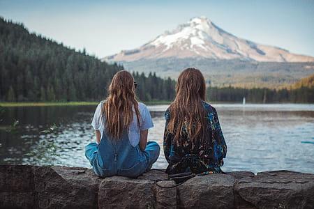 two woman sitting on rock near body of water