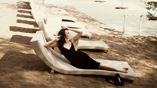 woman in recumbent position lying on bench in front ofbody of water