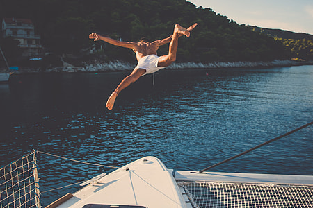 man in white shorts jumps on water