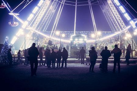 people standing near ferris wheel theme park ride during nighttime