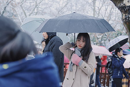 woman wears gray coat holds umbrella