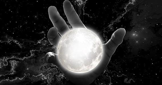 human hand holding moon