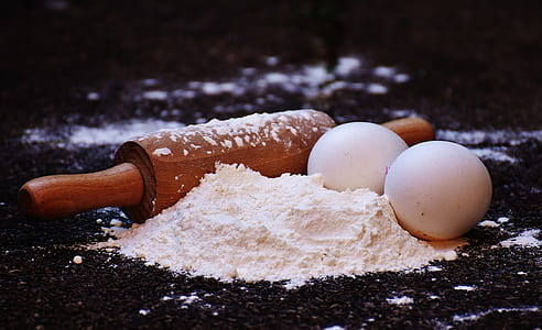 brown rolling pin and two white eggs