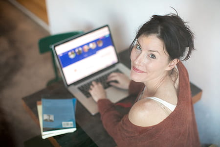 woman wearing brown off-shoulder sweatshirt while using MacBook