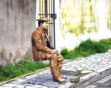 man in brown suit sitting