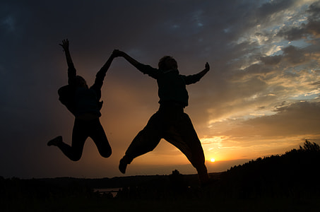 two person jumping while holding each other at daytime