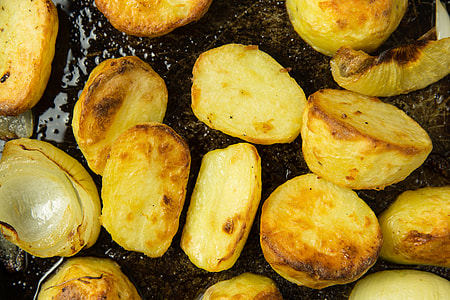 Roast potatoes and onions in baking tray