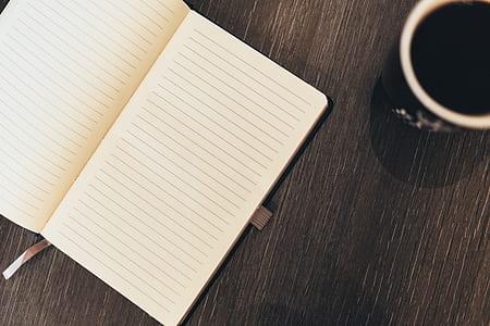 white book beside black ceramic mug