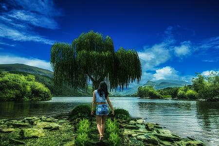 woman wearing blue sleeveless shirt standing near green willow tree