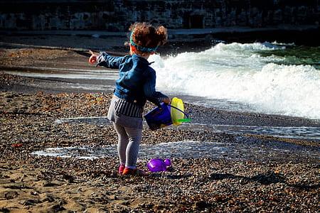 toddler in jacket holding bucket standing on seashore