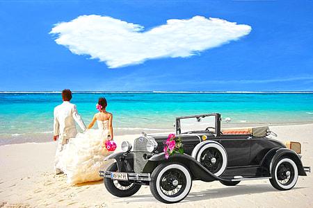 bride and groom beside black car on the beach photography