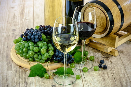 two wine glass beside grapes