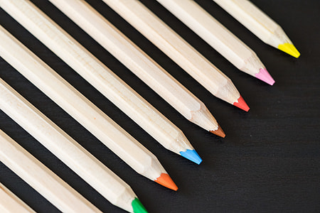 Long Colored Pencils in a Row on Black Desk