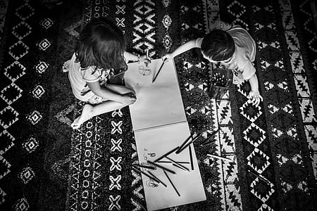 grayscale photography of two children holding color pens
