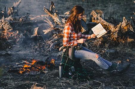 shallow focus photography of woman near bonfire reading book