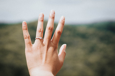left human's hands wearing diamond solitaire ring