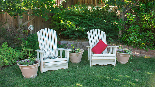 two white wooden lounge hairs on green lawn
