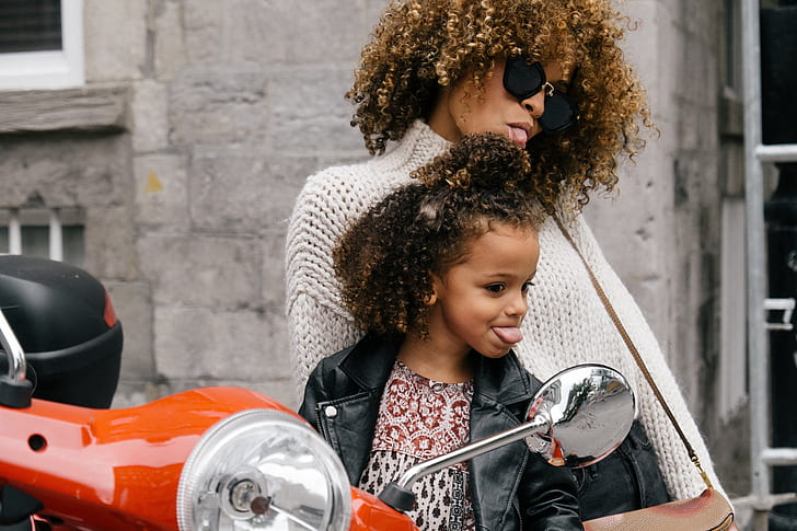 mother and girl riding motor scooter