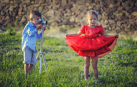 boy taking a photo of a girl wearing red dress