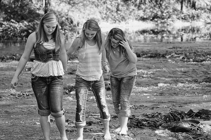 grayscale photo of three girls walking