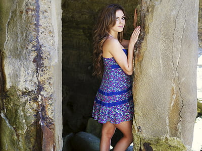 woman wearing blue and purple floral sleeveless dress beside gray concrete wall