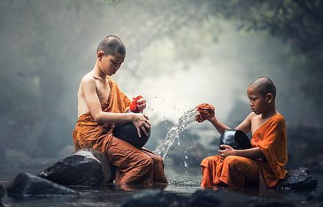 two children in orange dresses sitting on black rock