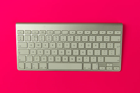 Apple wireless keyboard on pink background