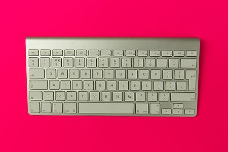 Apple wireless keyboard on pink background