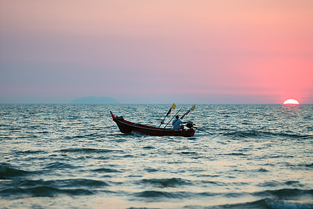 person riding on boat with sunset as background