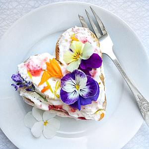heart-shape white icing cake beside gray fork on white ceramic plate