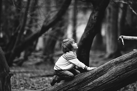 grayscale photography of child in sweater and pants