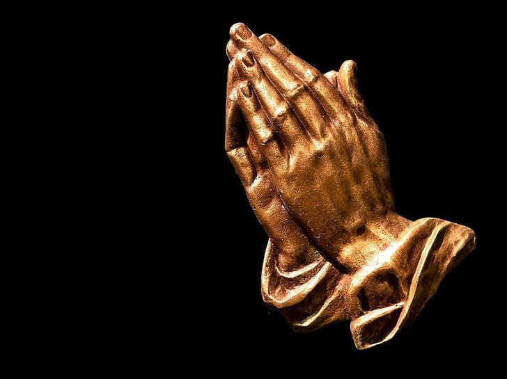 closeup photo of brass-colored praying hands figurine
