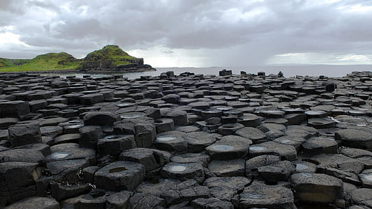 black rock formations under cloudy sky