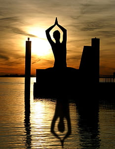 silhouette of person standing on body of water with dance gesture during golden hour