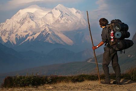 man in black shirt standing near mountain
